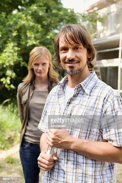 Man holding folding ruler, woman standing behind