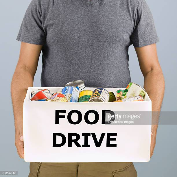 man holding food drive box - food drive stock pictures, royalty-free photos & images