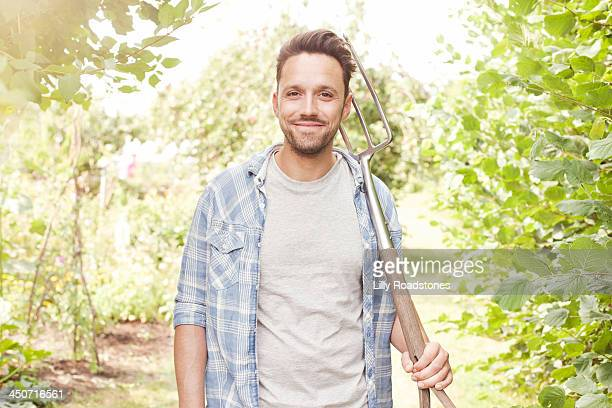 Man holding fork at entrance to allotment