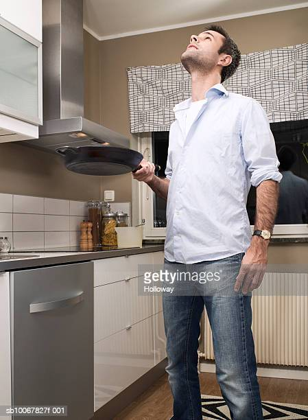 Man holding frying pan looking at ceiling in kitchen