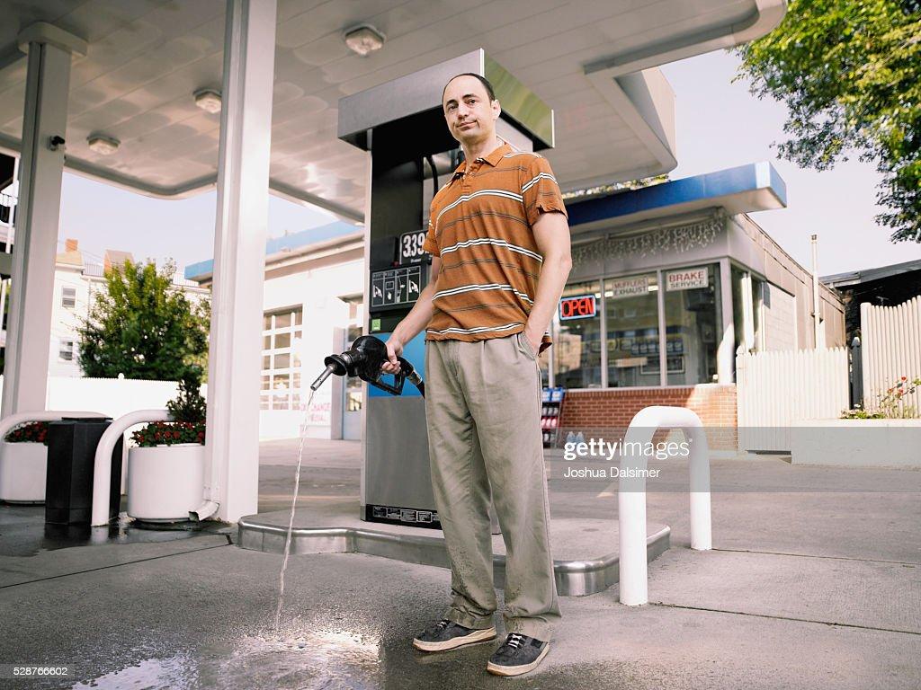 Man holding fuel pump : Stock Photo