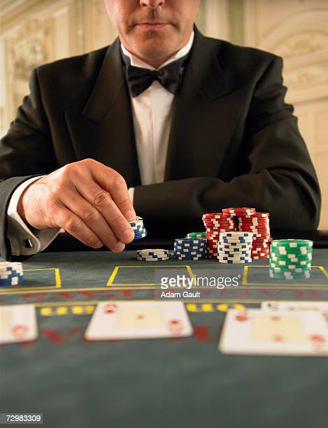 Man holding gambling chips in casino, mid section