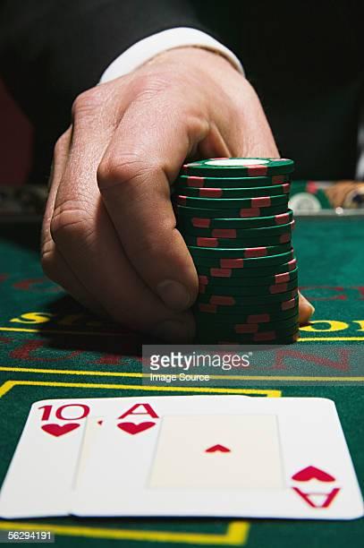 Man holding gambling chips with winning blackjack cards