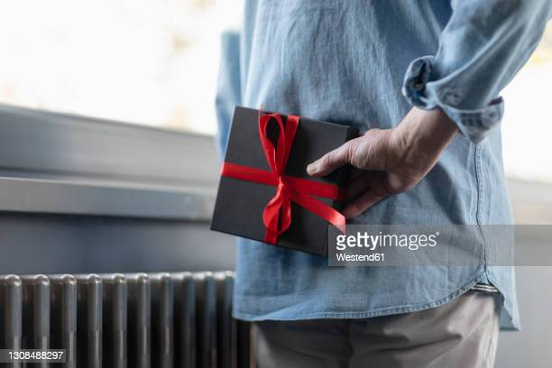 man holding gift box behind while standing at home - 後ろ手 ストックフォトと画像