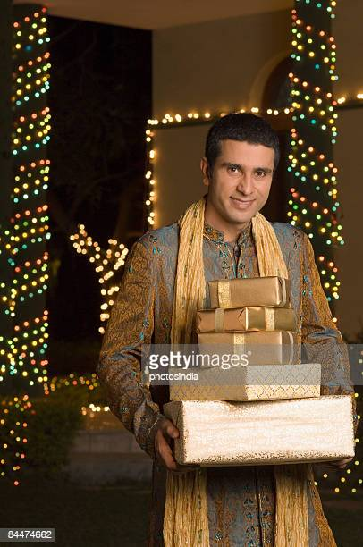 man holding gifts and smiling - kurta stock pictures, royalty-free photos & images