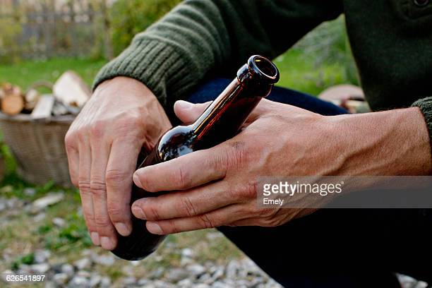Man holding glass beer bottle, close up