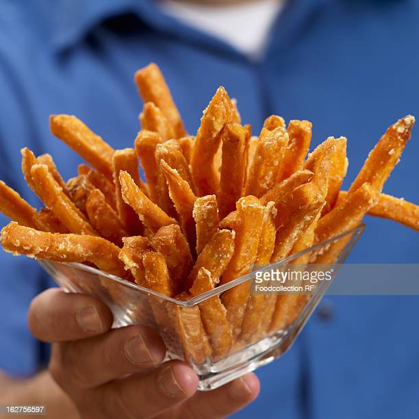 Man holding glass bowl of sweet potato fries