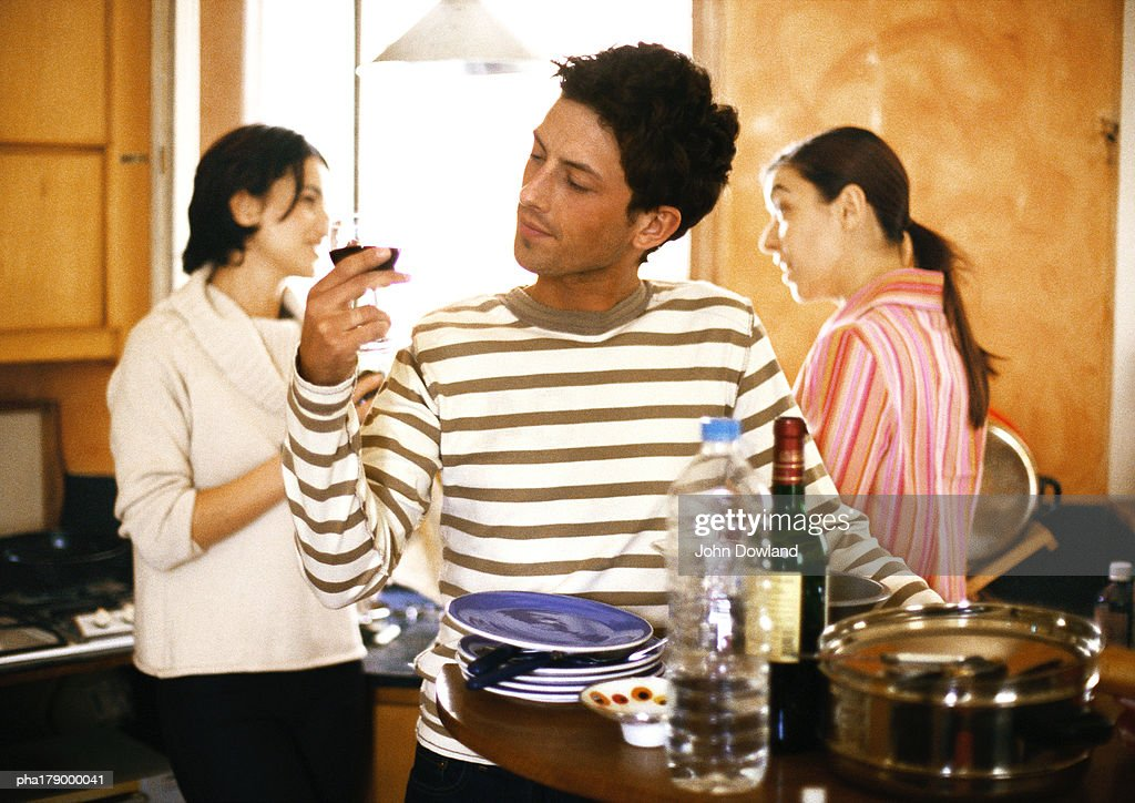 Man holding glass in kitchen, two women talking behind : Stockfoto