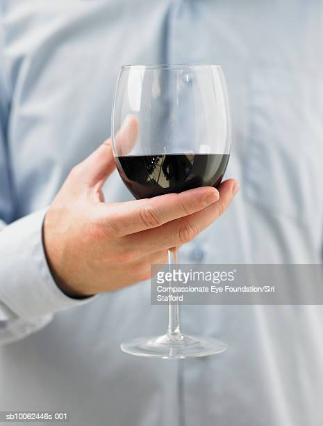 Man holding glass of red wine, mid section