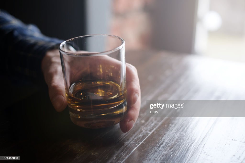 Man holding glass of whisky : Stock Photo