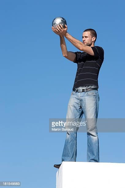 Mann hält Globus im Freien