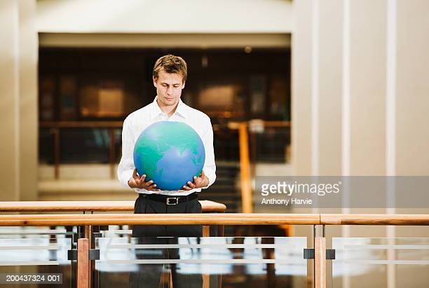 Man holding globe standing at balcony in office