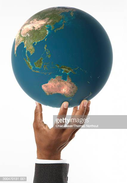 man holding globe with australia prominent (digital composite) - world at your fingertips stock pictures, royalty-free photos & images