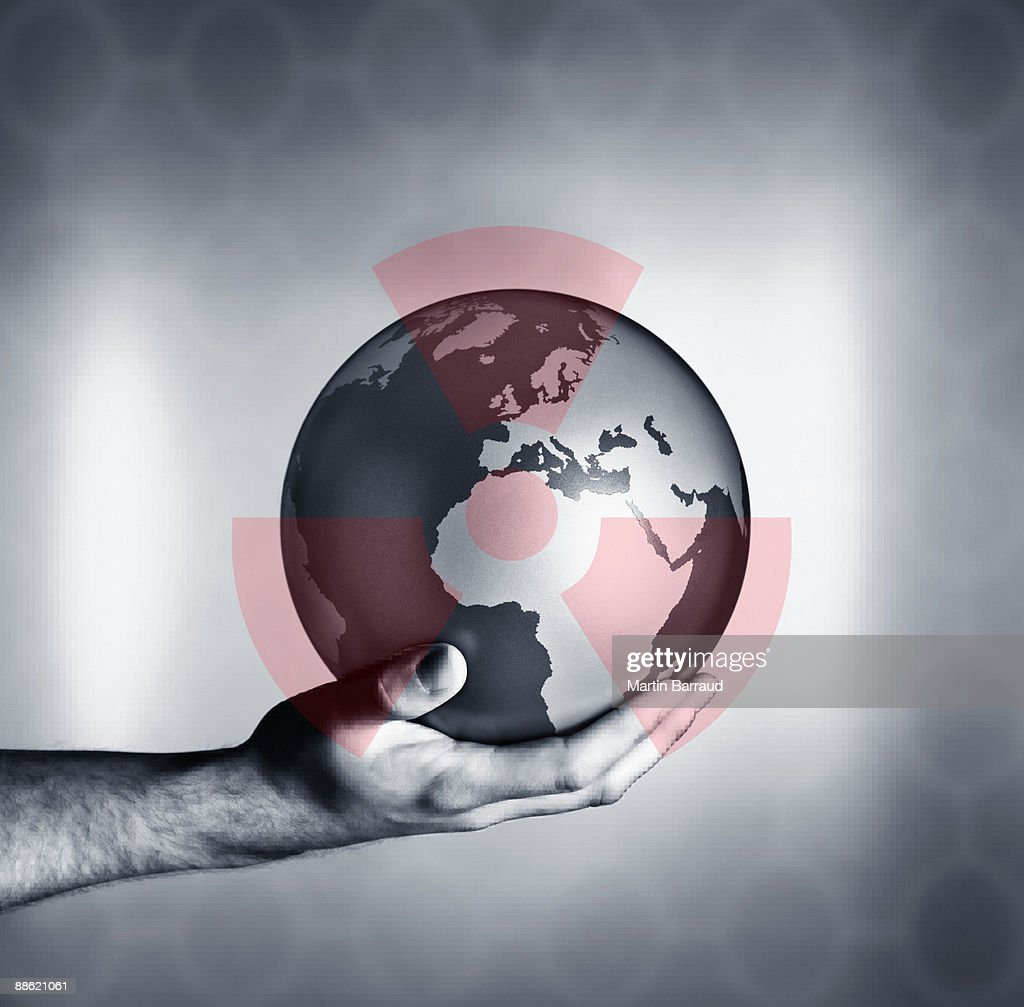 Man holding globe with overlay of nuclear symbol : Stock Photo