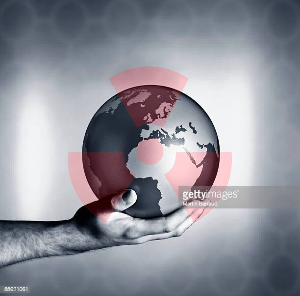 man holding globe with overlay of nuclear symbol - radioactive contamination stock pictures, royalty-free photos & images