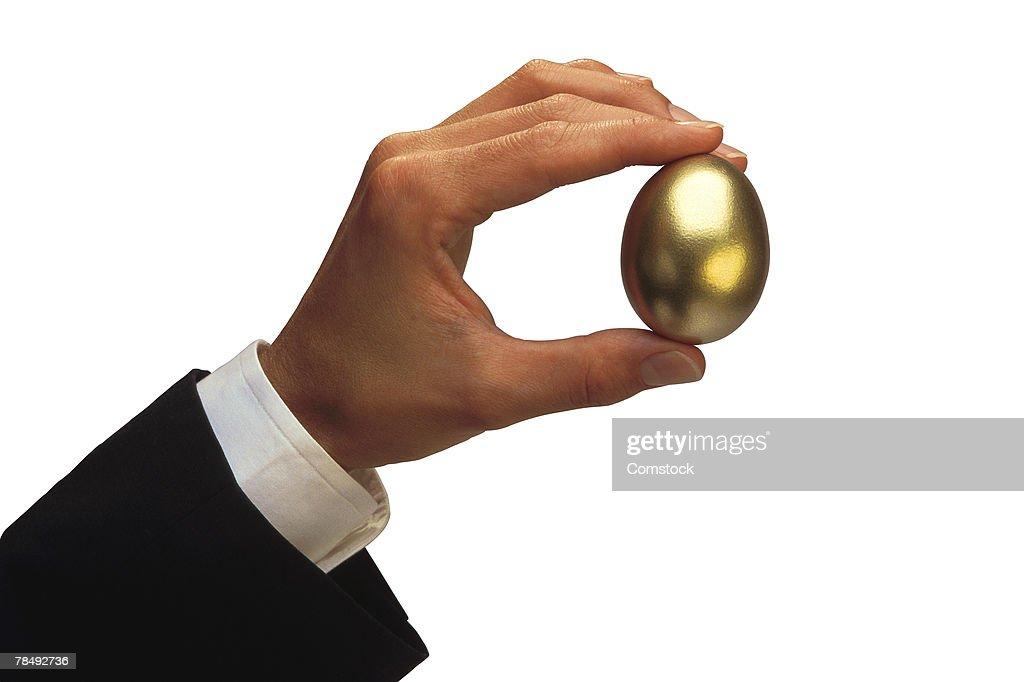 Man holding golden egg : Stock Photo