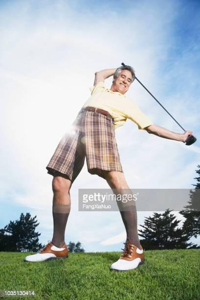 mann hält golfclub und stretching - golf lustig stock-fotos und bilder