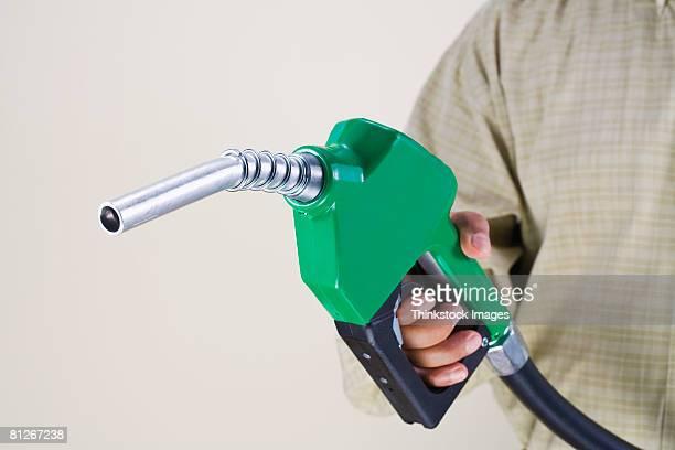 4e187260dfa4b Man holding green fuel pump nozzle
