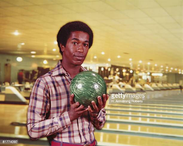 man holding green marbleized bowling ball in bowling alley, lanes in background. (photo by h. armstrong roberts/retrofile/getty images) - black alley stock photos and pictures