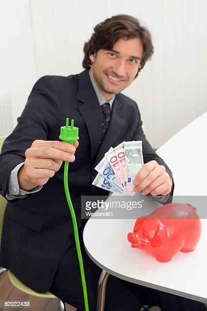 man holding green plug and banknotes - banconote euro foto e immagini stock