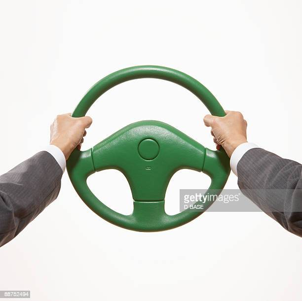 man holding  green steering wheel