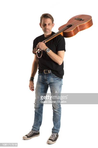 man holding guitar against white background - guitarist stock pictures, royalty-free photos & images