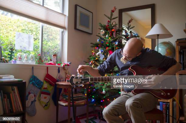 Man holding guitar at home during Christmas