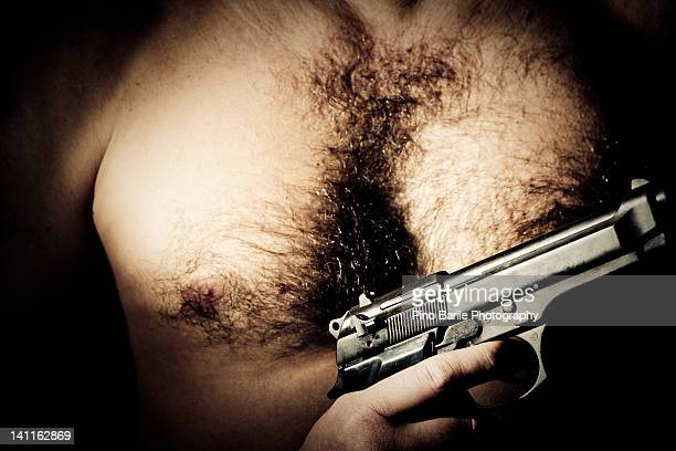 man holding gun - hairy man chest stock photos and pictures