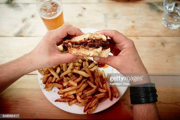 Man holding half eaten burger