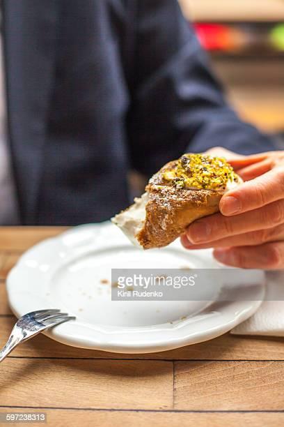 Man holding half eaten cannoli