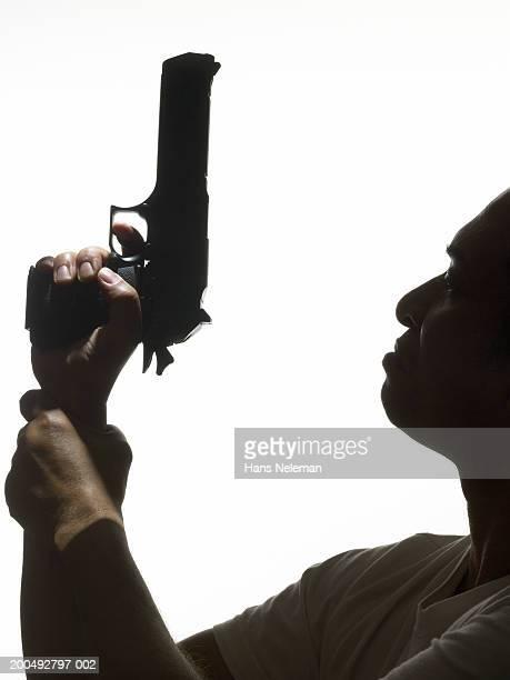 Man holding hand gun, close-up, profile