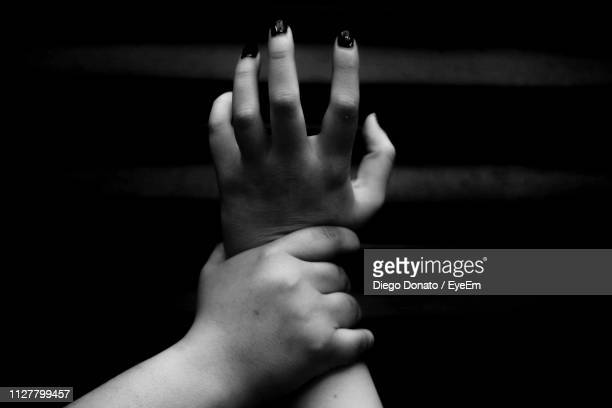 man holding hand of woman against black background - violenza foto e immagini stock