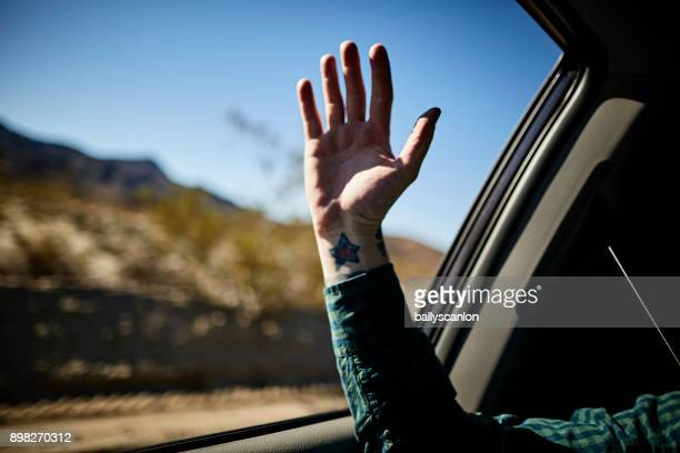 Man Holding Hand Out Car Window