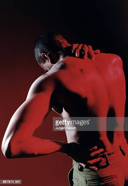 Man holding hand round back of neck, rear view (red tone)