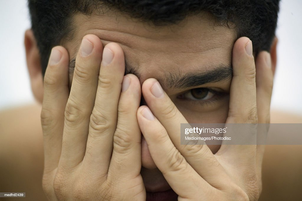 Man holding hands in front of face, extreme close-up, part of : Stock Photo