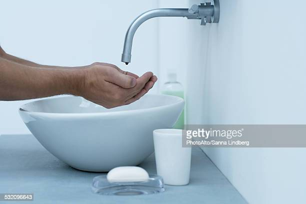 Man holding hands under dripping faucet in bathroom sink, cropped