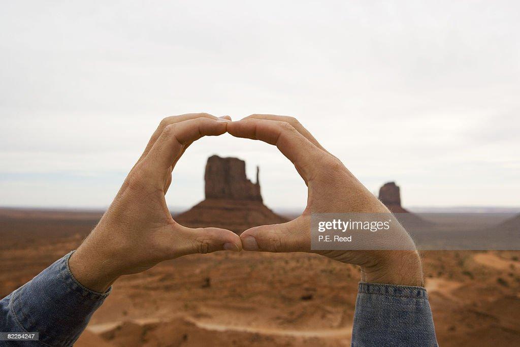 Man Holding Hands up around Mitten Butte : Stock Photo