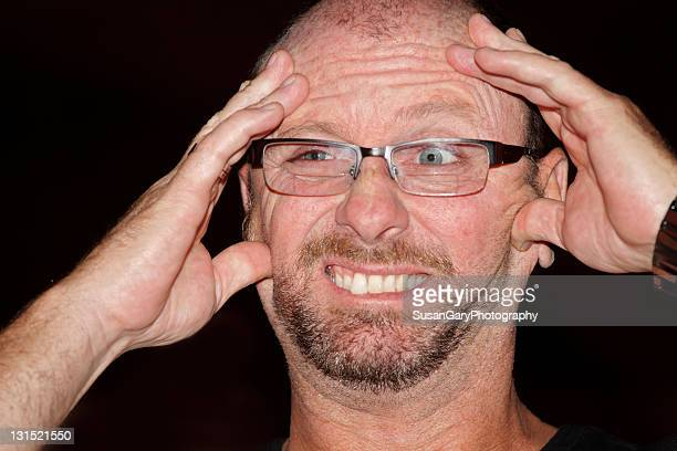 Man holding head and making funny face