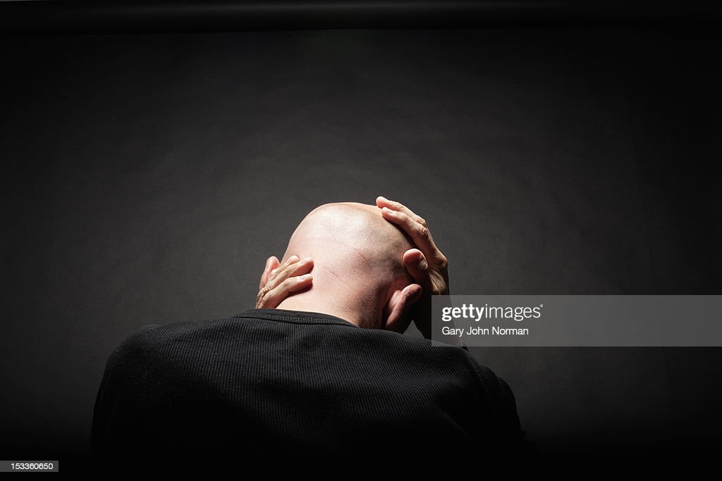 man holding head in hands rear view : Stock Photo
