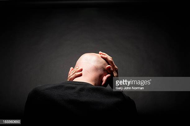 man holding head in hands rear view - completely bald stock pictures, royalty-free photos & images