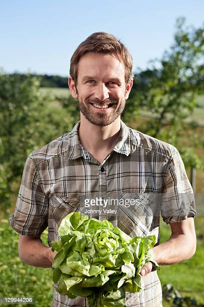 Man holding head of lettuce outdoors