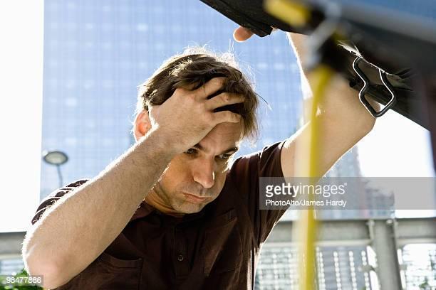 Man holding head, raising hood of car