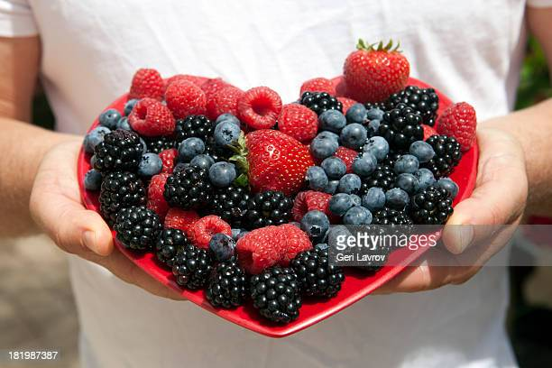Man holding heart shaped plate of berries