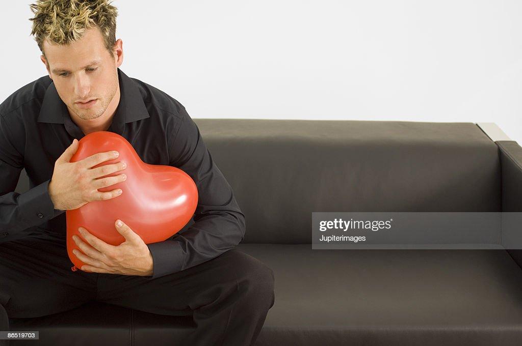 Man holding heart-shaped balloon : Stock Photo