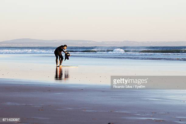 Man Holding Helmet While Bending On Sea Shore Against Clear Sky