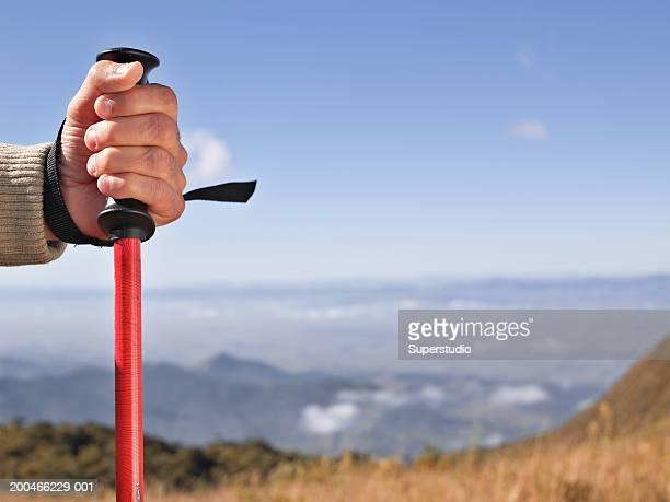 Man holding hiking pole, close-up