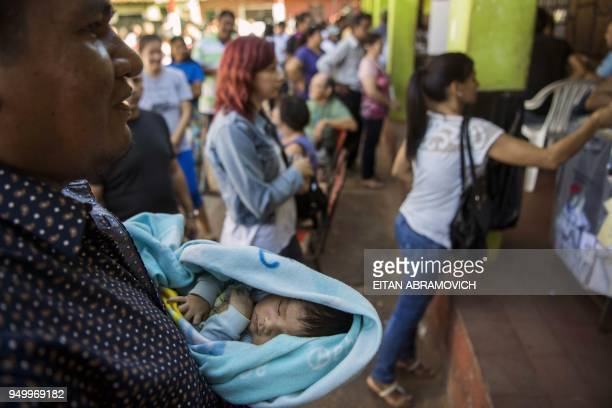 A man holding his baby queues to vote at a polling station in Mariano Roque Alonso outskirts of Asuncion on April 22 during Paraguay's presidential...