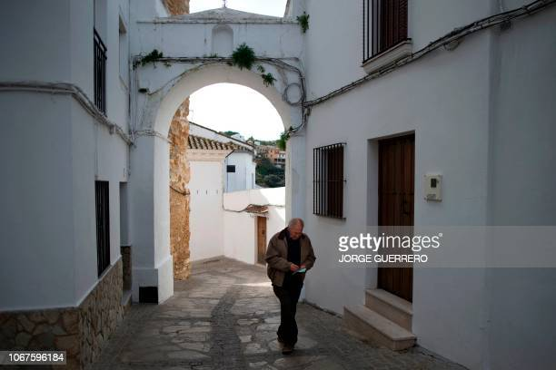 Man holding his ballot walks in Setenil de las Bodegas near Cadiz on December 2, 2018 during Andalusia's regional election.