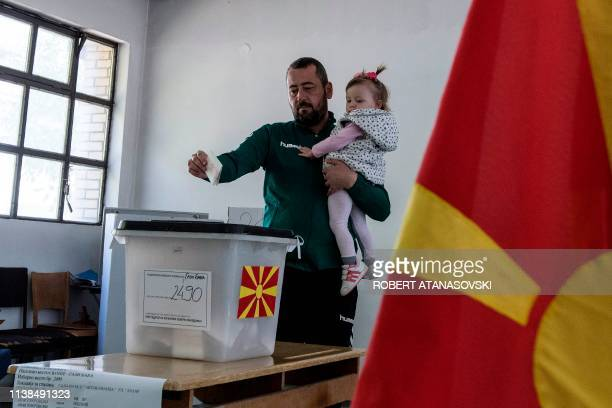 Man holding his child casts his ballot for the presidential election at a polling station in Skopje on April 21, 2019. - North Macedonians voted for...