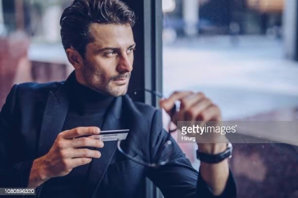 homme tenant sa carte de crédit - col roulé photos et images de collection